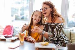 Mãe ruivo que come sobremesas doces com filha Fotos de Stock Royalty Free