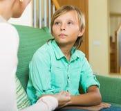 Mãe séria e menino adolescente que falam na casa Foto de Stock
