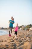 Mãe saudável e bebê que correm na praia Fotografia de Stock