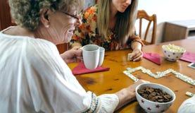Mãe superior e filha que jogam o dominó Fotos de Stock