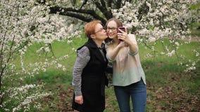 Mãe superior e sua filha adulta que tomam o selfie no jardim de florescência video estoque