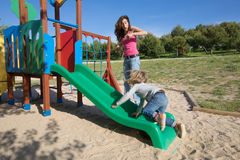 Mãe surpreendida pela criança que desliza na corrediça verde Imagem de Stock Royalty Free