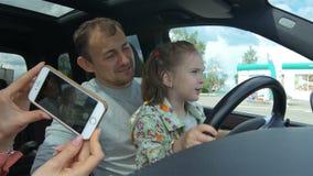 A mãe toma a foto da filha de ensino do marido para conduzir filme