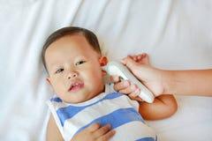 A mãe toma a temperatura para o infante com o termômetro de orelha na cama em casa fotografia de stock royalty free