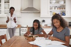 A mãe usa o telefone como filhas Sit At Table Doing Homework foto de stock royalty free