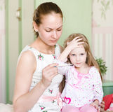A mãe verifica a temperatura na criança Imagem de Stock