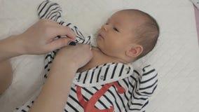 A mãe veste um bebê recém-nascido video estoque