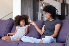 Mãe virada e filha afro-americanos que discutem em casa imagem de stock royalty free
