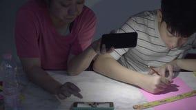 Mães asiáticas ajudam meu filho a fazer arte usando a luz do telefone para terminar o trabalho filme