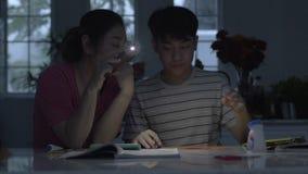Mães asiáticas ajudam meu filho a fazer arte usando a luz do telefone para terminar o trabalho video estoque