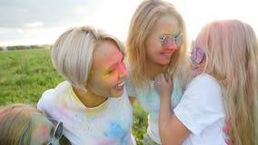 Mães felizes com as crianças que têm o divertimento com pó colorido no festival do holi das cores filme