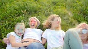 Mães felizes com as crianças que têm o divertimento com pó colorido no festival do holi das cores vídeos de arquivo
