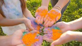 Mães felizes com as crianças que têm o divertimento com pó colorido no festival do holi das cores video estoque