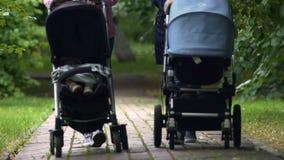 Mães que andam no parque com os bebês nos carrinhos de criança, pagamento de maternidade, paternidade filme