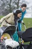 Mães que olham nos carrinhos de criança no parque Imagem de Stock
