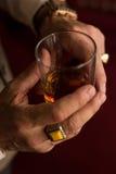 Mão à moda do ` s do homem com um anel no dedo pequeno e em um vidro do uísque em sua mão foto de stock royalty free