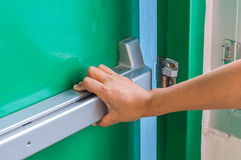A mão é empurrar/que abre a porta da saída de emergência da emergência Fotos de Stock