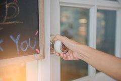 A mão abre o botão de porta branco ou a abertura da porta fotografia de stock