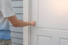 A mão abre o botão de porta branco ou a abertura da porta fotos de stock