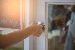 A mão abre o botão de porta branco ou a abertura da porta foto de stock
