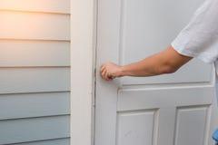A mão abre o botão de porta branco ou a abertura da porta imagens de stock