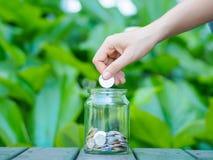 A mão abstrata das mulheres da economia do dinheiro pôs a moeda ao frasco de vidro Fotografia de Stock Royalty Free