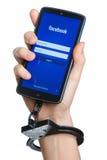 Mão acorrentada com smartphone onde o facebook app começou Foto de Stock Royalty Free