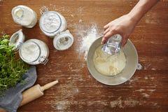 A mão adiciona a água à massa caseiro da farinha que faz a farinha da massa Fotografia de Stock Royalty Free
