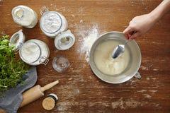 A mão adiciona ingeredients com a colher na massa da farinha da bacia Imagens de Stock