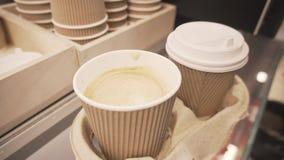 A mão agita o açúcar com a colher no copo descartável do café e de cobri-lo do latte da soja com a tampa plástica filme