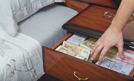 A mão alcança para o dinheiro na tabela de cabeceira Foto de Stock