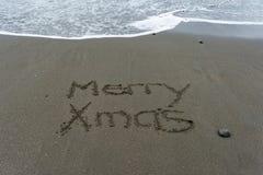 Mão alegre do Xmas escrita na areia com o mar no backgrou imagens de stock