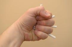 A mão aperta um punho e esmaga os cigarros para parar de fumar Fotos de Stock Royalty Free