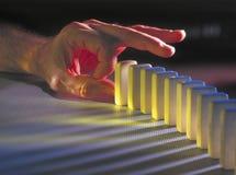 Mão aproximadamente para bater para baixo dominós foto de stock