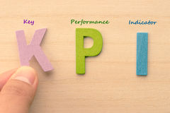 A mão arranja letras como KPI imagens de stock