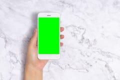 Mão ascendente próxima da mulher que guarda o telefone celular branco com a tela verde vazia no fundo de mármore branco, vista di fotografia de stock