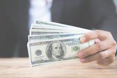 Mão ascendente próxima do homem de negócios que guarda notas de dólar do dinheiro na tabela de madeira fotografia de stock