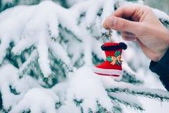 Mão ascendente próxima do homem que guarda botas de Santa do brinquedo do Natal na frente da árvore de Natal coberto de neve do a fotografia de stock