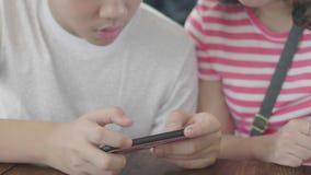 Mão ascendente próxima do menino asiático que usa-se no telefone esperto móvel video estoque