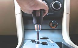 Mão ascendente próxima que guarda para mudar a engrenagem dentro de um carro foto de stock