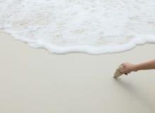 Mão asiática da mulher que guarda a pedra do mar branco no canto na praia branca limpa e vazia da areia com a onda do mar como o  Imagens de Stock