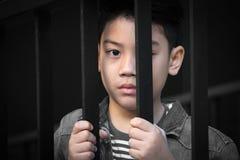 Mão asiática do menino na cadeia que olha para fora a janela Imagens de Stock