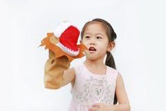 Mão asiática pequena bonito da menina da criança que veste e que joga fantoches do leão no fundo branco, cabeça do leão fotografia de stock royalty free