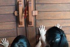 A mão asiática pequena de duas meninas pôs sobre a porta de madeira com envelope vermelho fotos de stock royalty free