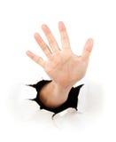 Mão através de um furo no papel imagens de stock
