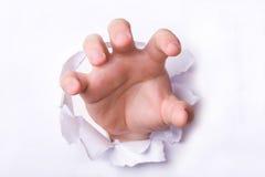 Mão através do papel Imagens de Stock