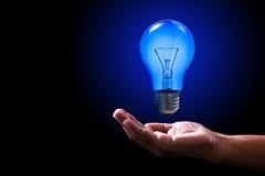 Mão azul brilhante do ser humano da ampola e do poder foto de stock