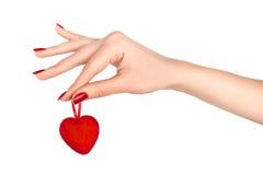 Mão bonita com o tratamento de mãos vermelho que guarda o coração vermelho. Imagem de Stock Royalty Free