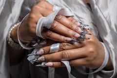 Mão bonita da menina com enxerto de pele escuro de pregos acrílicos com o fotmoy incomum do prego Foto de Stock