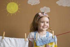 A mão bonita pequena da menina que põe o pregador de roupa e pendura para fora para secar a roupa Trabalhos domésticos conceptuai Fotografia de Stock